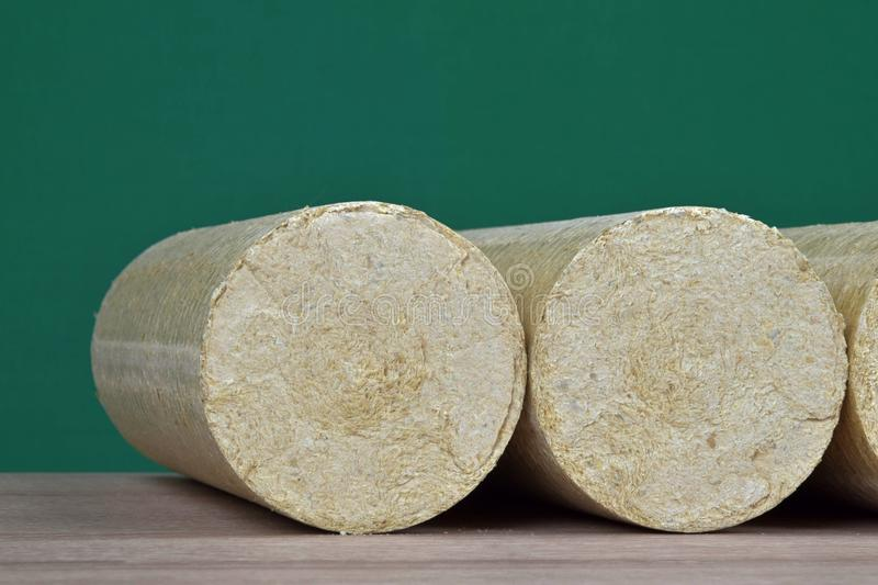 Wood sawdust briquettes straightened, green background. Alternative fuel, bio fuel.  royalty free stock images