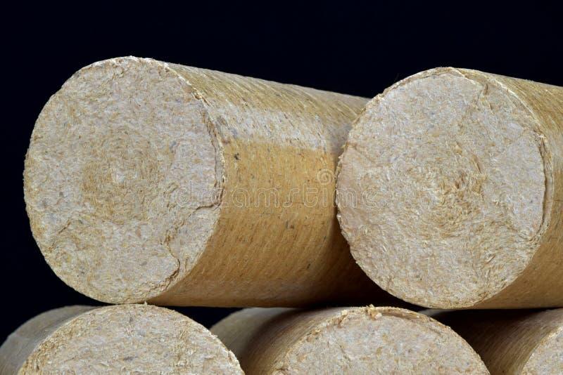 Wood sawdust eco-briquettes straightened, black background. Alternative fuel, bio fuel.  stock images