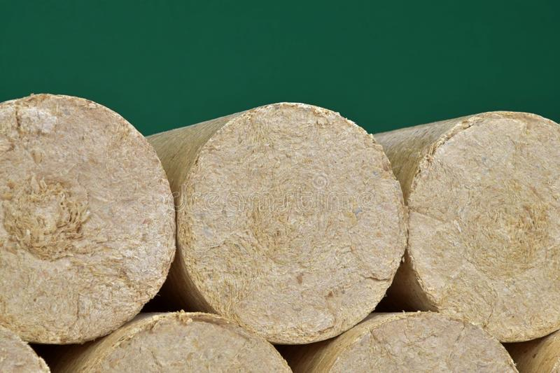 Wood sawdust eco-briquettes straightened, green background. Alternative fuel, bio fuel.  royalty free stock images