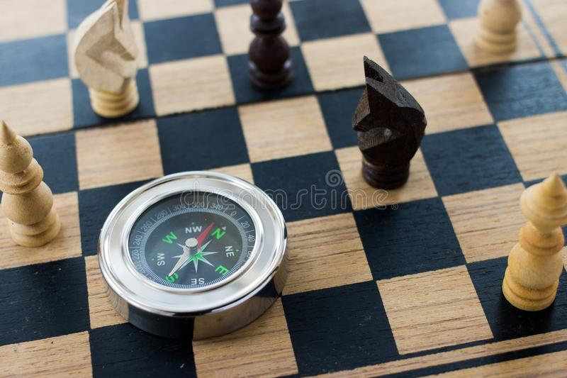 Wood schack och kompass på den gamla wood schackbrädet av affärsdirec arkivfoton