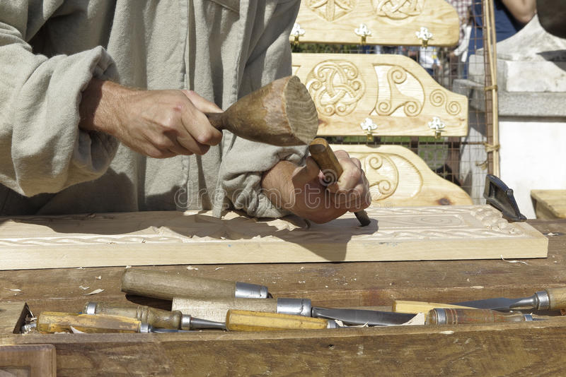 Wood sculptor. Forefront of hands of a wood sculptor carving wood royalty free stock image