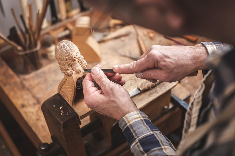 Wood sculptor at a workbench carving a wooden figure royalty free stock photo