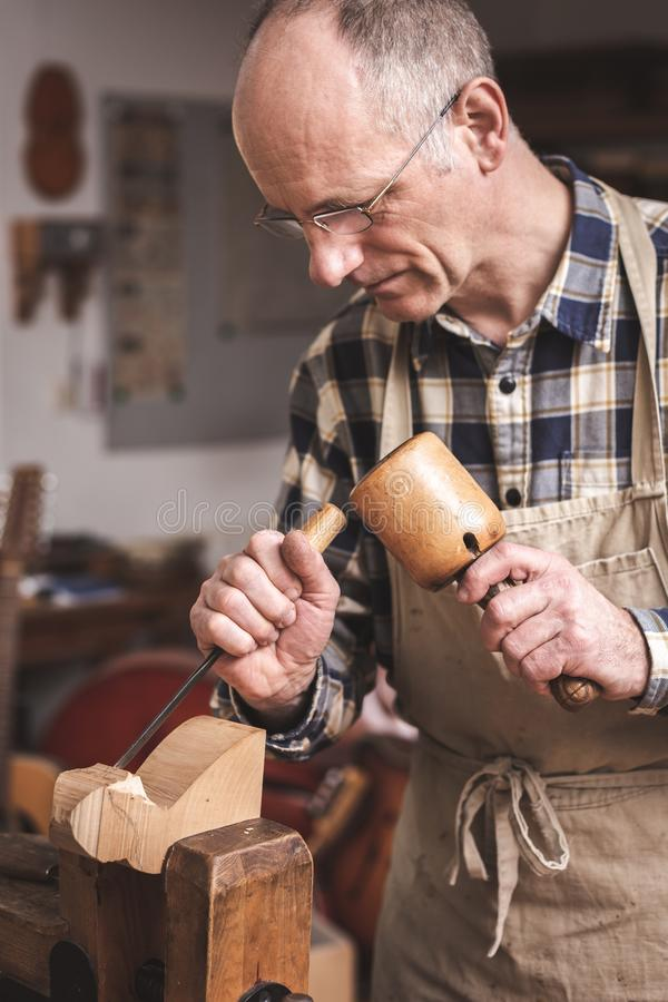 Wood sculptor working with chisel and mallet. A mature man is working with carving tools on a piece of wood. He is wearing an apron and a checkered shirt stock photography