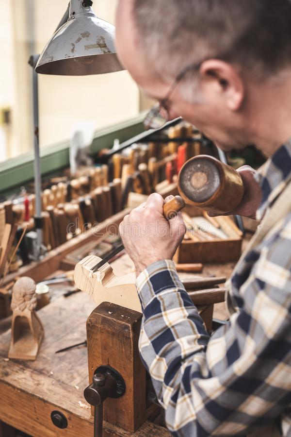 Wood sculptor working with mallet and chisel. A mature man is working with carving tools on a piece of wood. He is wearing a checkered shirt standing inside a stock photography
