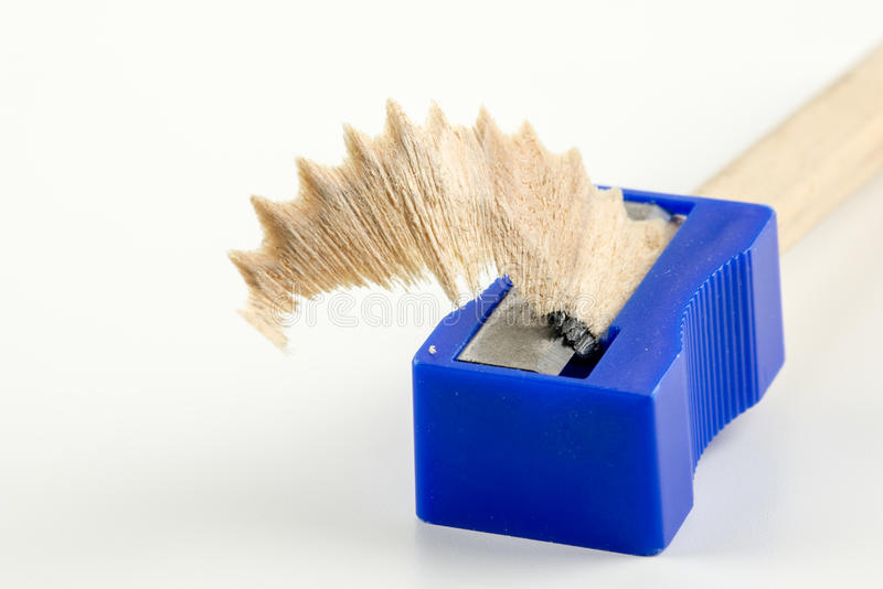 Wood shaving in a pencil sharpener. Textured wood shaving in a pencil sharpener with graphite from sharpening the accompanying wooden pencil on a white royalty free stock photos