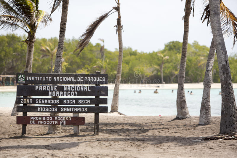 Wood sign to the paradise beach, Venezuela. MORROCOY, VENEZUELA, APRIL 24: Entrance wood sign to the beach with unrecognizable people swimming in the background royalty free stock photos