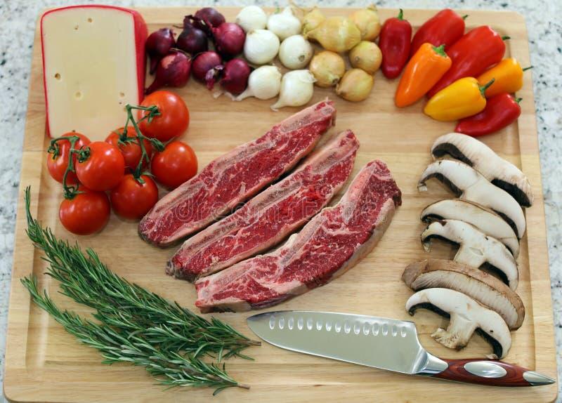 Wood skärbräda i köksbord med korta stöd för nötkött, rosmarin, champinjoner, tomater, ost, lökar och peppar arkivbilder