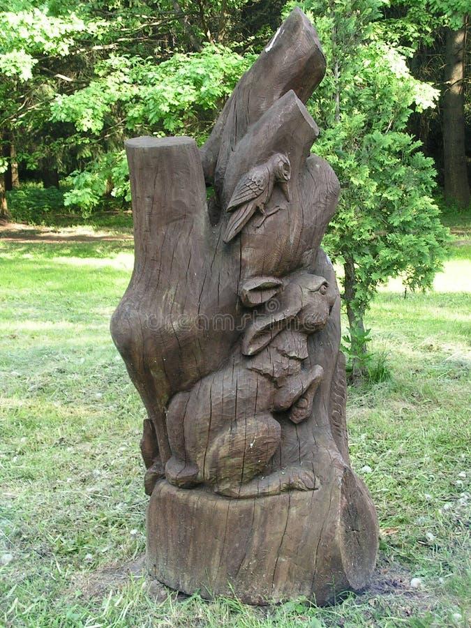 Wood skulptur Skoganvändare Landskapomr?de i str?larna av inst?llningssolen royaltyfria bilder