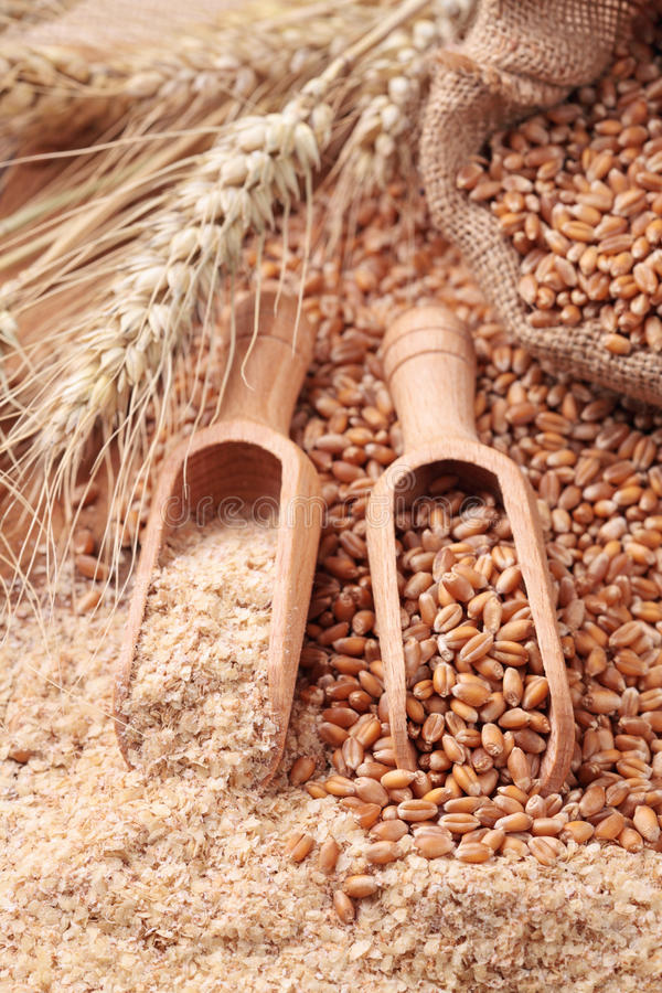 Wood spoon. With whole wheat grains stock photo