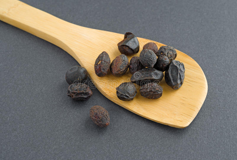 Wood spoon filed with saw palmetto berries. A wood spoon with saw palmetto berries on a dark background stock image