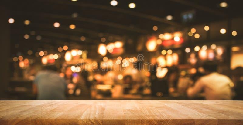 Wood stång för tabellöverkant med suddighetsljusbokeh i mörkt nattkafé fotografering för bildbyråer