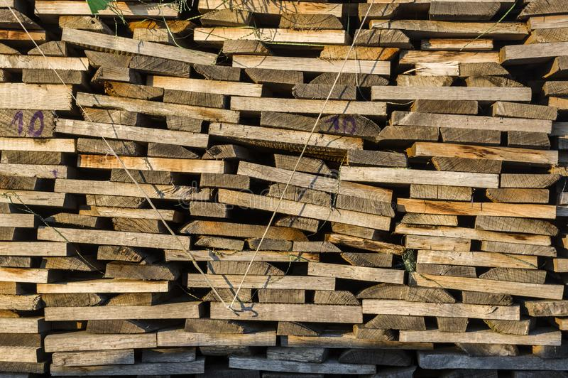 Wood stack of neatly stacked firewood and boards for drying fire royalty free stock images