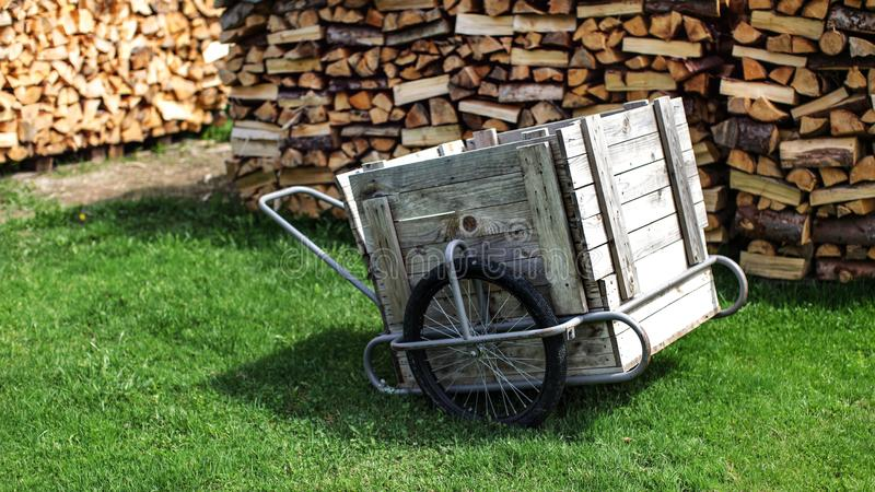 Wood and steel cart with rubber tires, on a green lawn, with piles of stacked chopped firewood in background. royalty free stock image