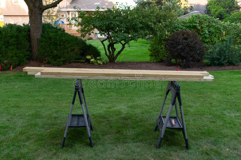 Wood on Supports in a Backyard for a Home Improvement Project. Pieces of wood on supports in a residential backyard with green grass for a home improvement stock photos