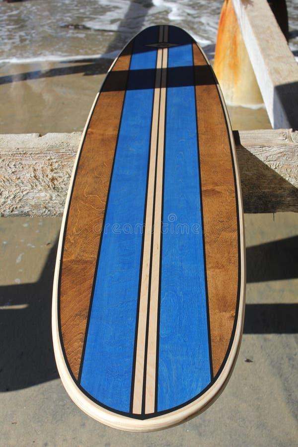 Wood surfingbräda mot den Kalifornien strandpir arkivfoto