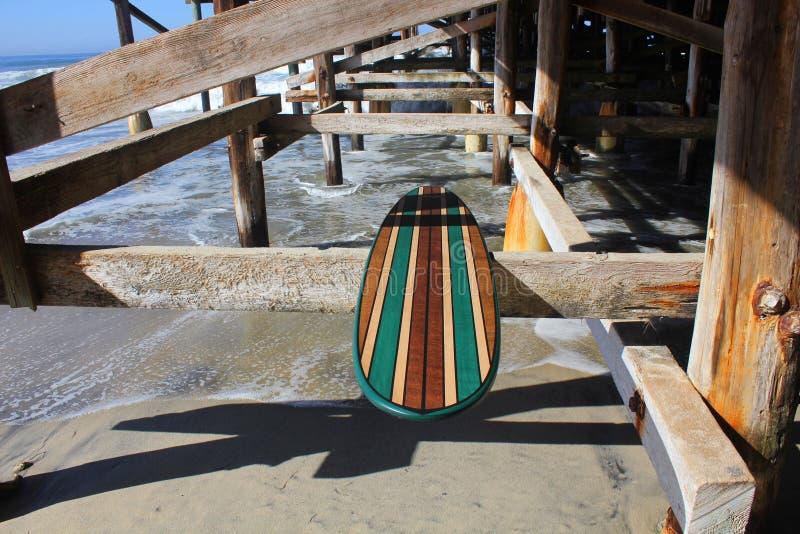 Wood surfingbräda mot den Kalifornien strandpir arkivbilder