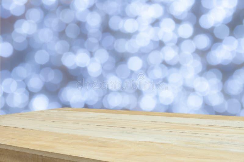 Wood tabell framme av vita bokehljus arkivfoton