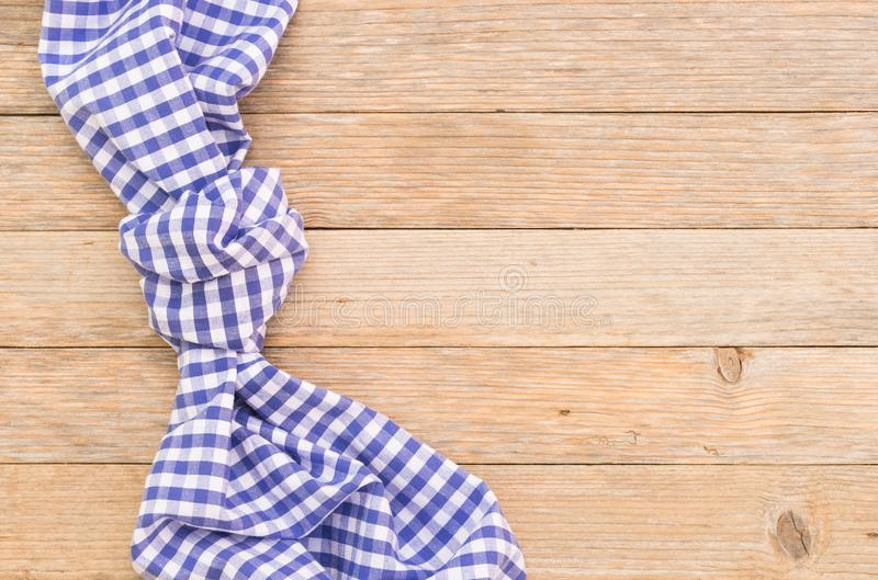 Wooden table background with rustic blue knotted tablecloth, top view, copy space. Wood table background with blue checkered tablecloth, high angel view royalty free stock photography