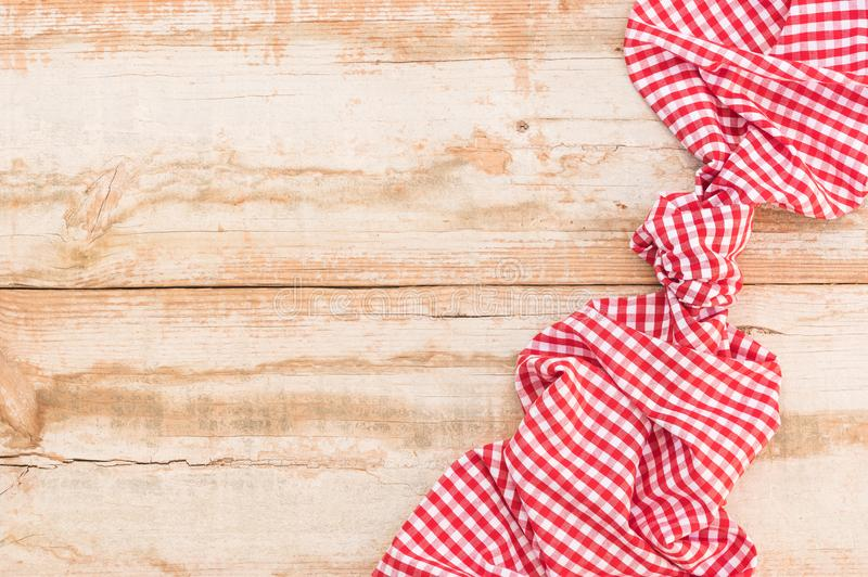 Vintage wooden table background with knotted red tablecloth, top view, copy space. Wood table background rustic texture, with red checkered tablecloth, high stock image