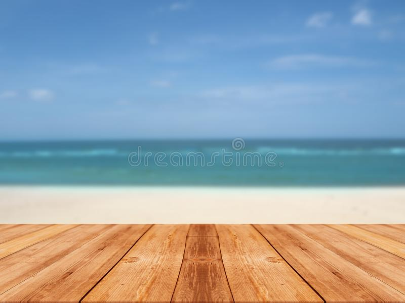 Wood table at beach and blur light bulb for background royalty free stock images