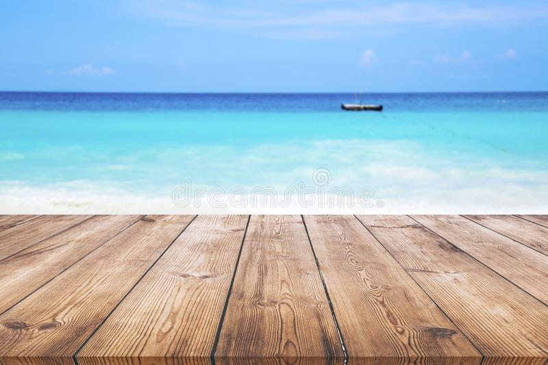 Wood table with blue sea and sand beach background royalty free stock photography