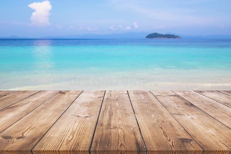 Wood table with blue sea and sand beach background stock image