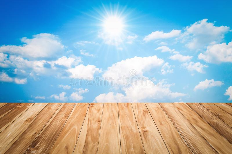 wood table and blue sky with sun stock photo