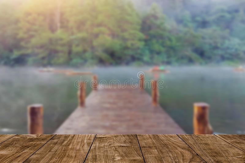 Wood table with blur wood bridge dock lake travel background royalty free stock photo