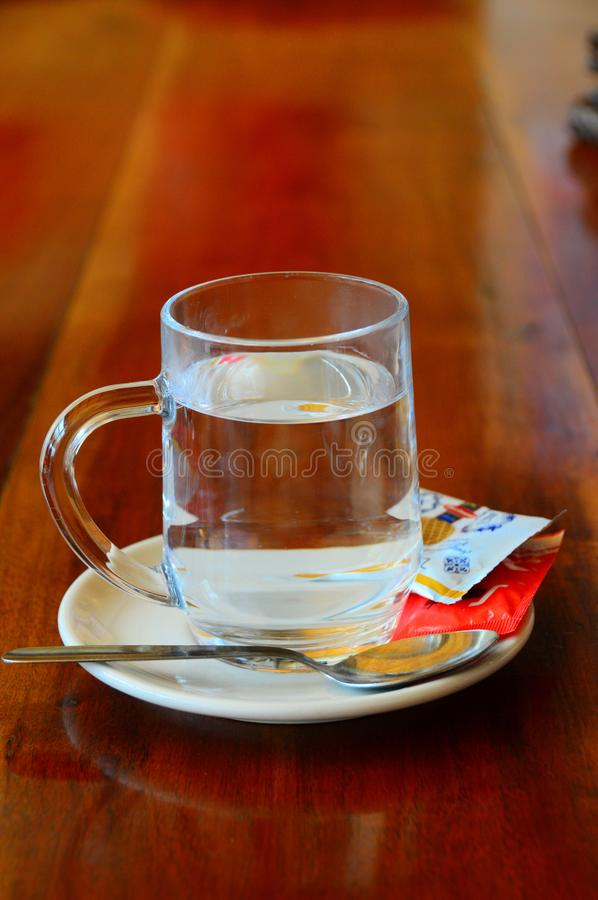 Glass cup of water on saucer with tea spoon tea bag and sugar royalty free stock photos