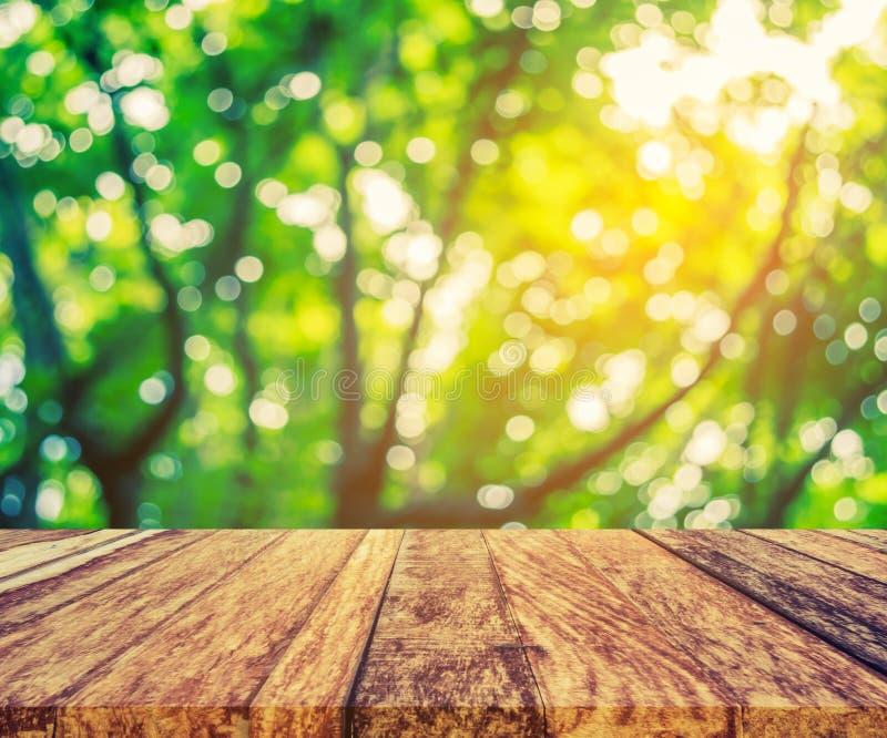 wood table and green tree bokeh stock image
