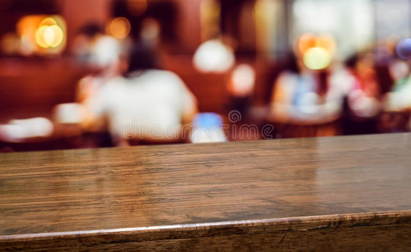 Wood table with people dinner at restaurant blur background.Empty perspective hardwood bar with blur coffee shop with bokeh light, royalty free stock photo