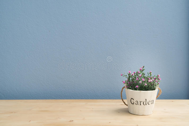 Wood table with pink rose on flower pot and blue cement wall. Wood table with pink rose on flower pot and blue cement wall, Left copy space area stock image