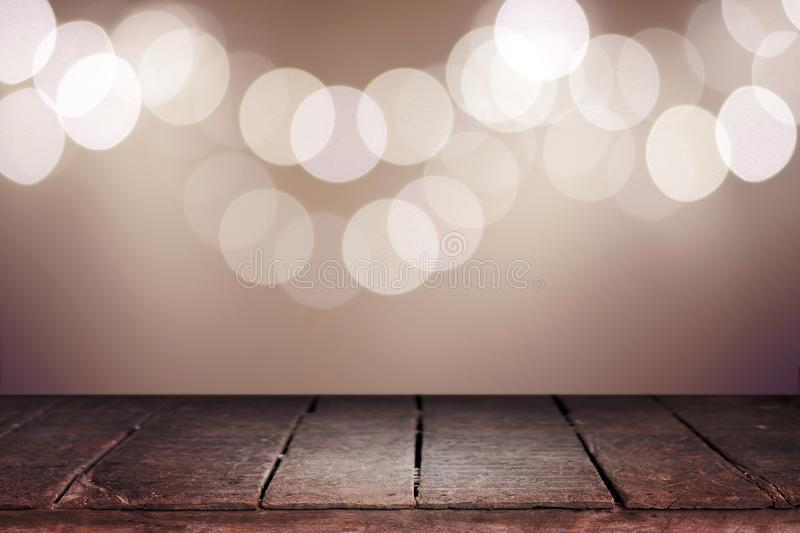 Wood table top on abstract bokeh background of lights. For Happy New Year and Merry Christmas vintage tone royalty free stock photo