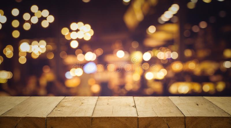 Wood table top Bar with blur light bokeh in dark night cafe. Restaurant background .Lifestyle and celebration concepts ideas stock images