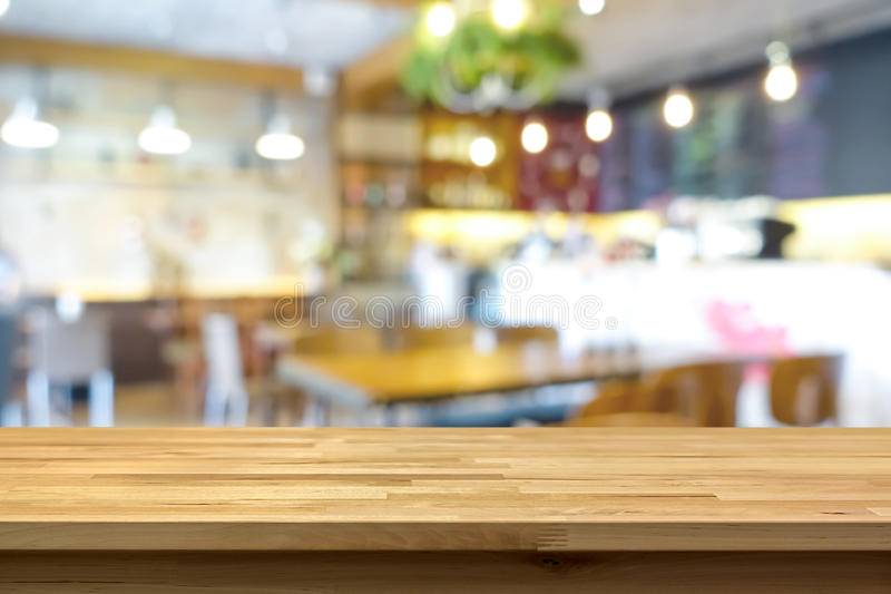 Wood table top on blur background of coffee shop (or restaurant) interior. Can be used for display or montage your products stock images