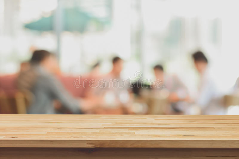 Wood table top on blur background of people in coffee shop. Soft tone - can be used for display or montage your products royalty free stock photography