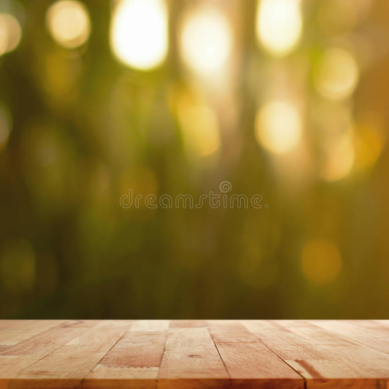 Wood table top on blur dark green background with bokeh effect. Can used for display or montage your products royalty free stock photos