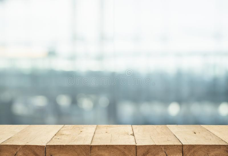 Wood table top on blur glass window wall building background. For montage product display or design key visual layout background royalty free stock photography