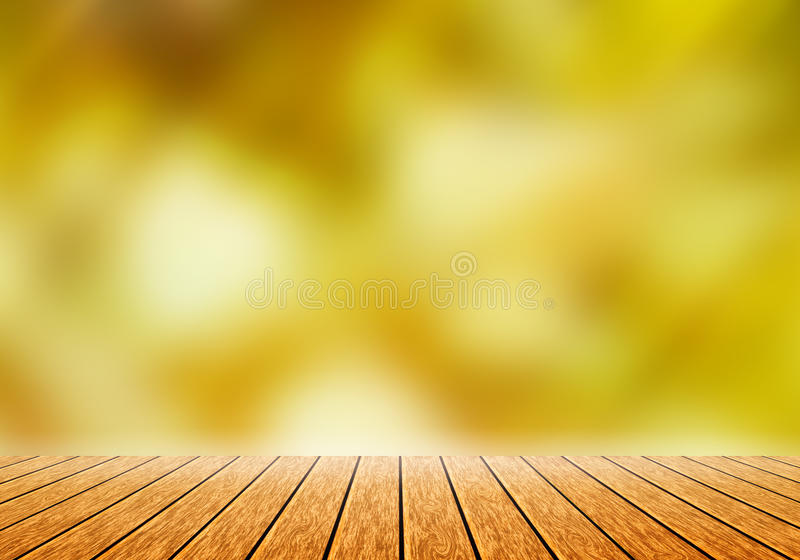 Wood table top with blur gold nature bokeh background. Can use for magazine or put any word on it stock image
