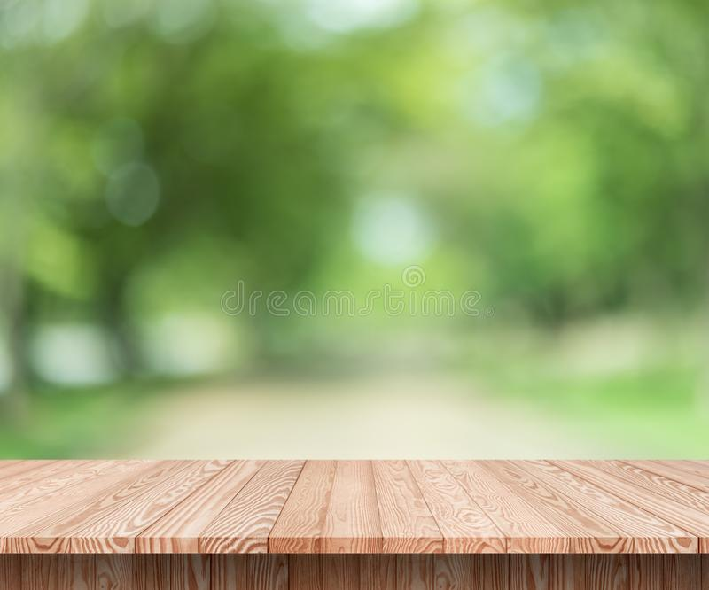 Wood table top on blur green background of trees in the park. stock photography