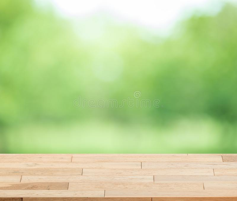Wood table top on blur green background of trees in the park. royalty free stock photo