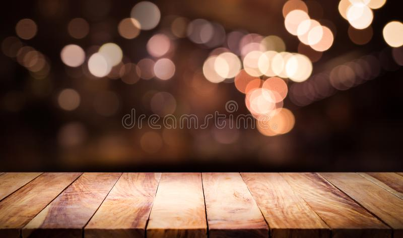 Wood table top with blur light bokeh in dark night cafe. Restaurant background .Lifestyle and celebration concepts royalty free stock photo