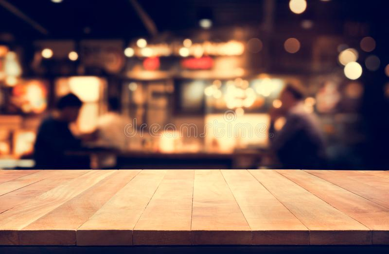 Wood table top with blur light bokeh in night cafe background. Lifestyle and celebration concepts royalty free stock photography