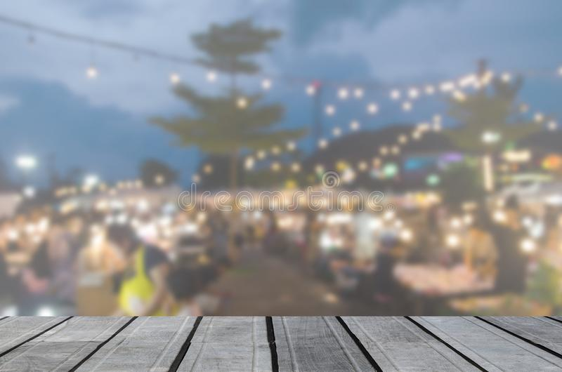 wood table top and Blur night Market Festival royalty free stock photo