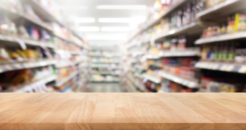 Wood table top on blur of supermarket product shelf background. stock photo