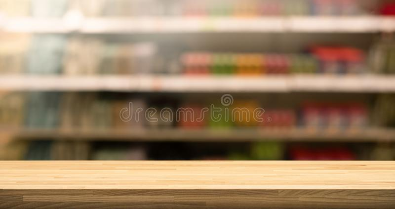 Wood table top on blur of supermarket product shelf background stock photography