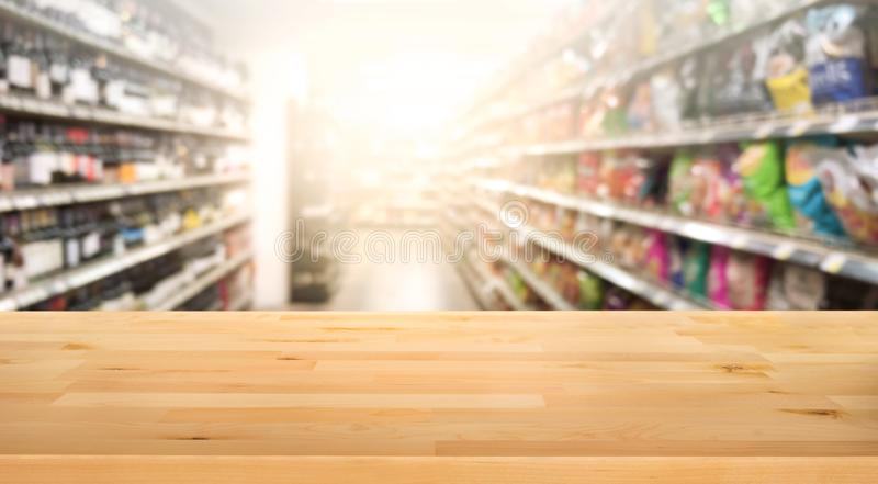 Wood table top on blur of supermarket product shelf background. stock photography