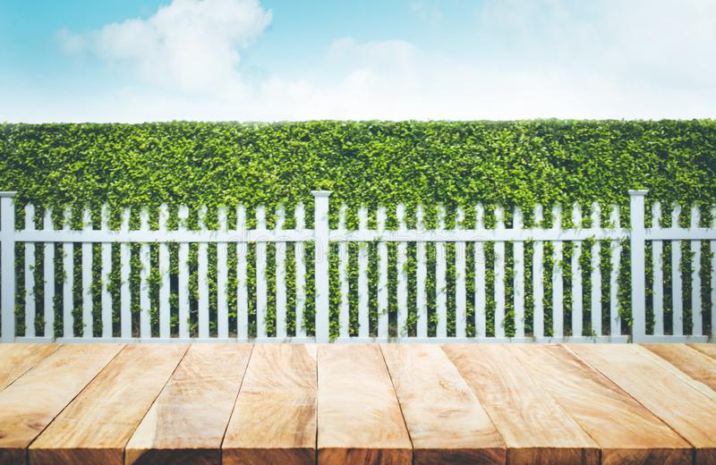 Wood table top on blur of white fence and garden background. For montage product display or design key visual layout stock photo