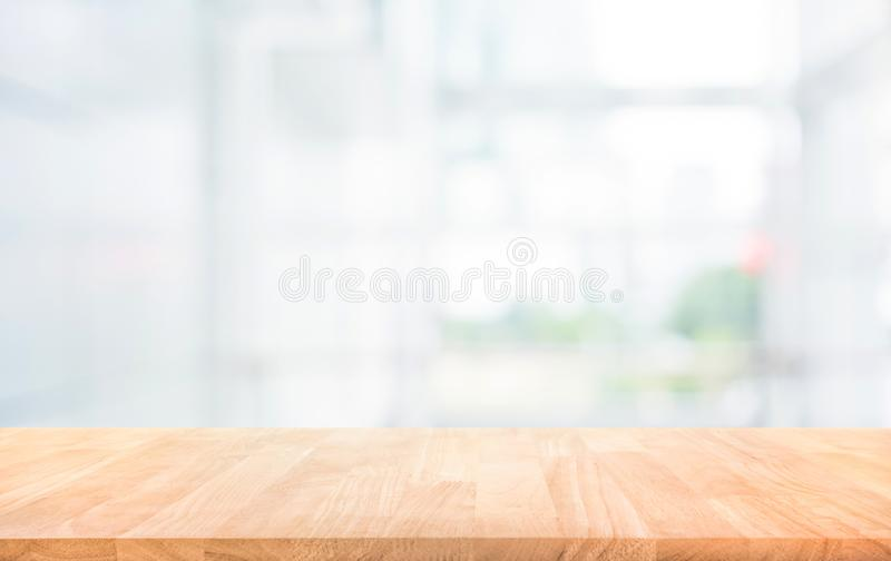Wood table top on blur white glass wall background form office. Building.For montage product display and design key visual layout stock image