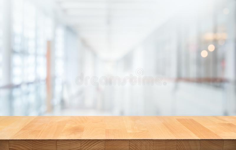 Wood table top on blur white glass wall background form office building. For montage product display and design key visual layout royalty free stock image
